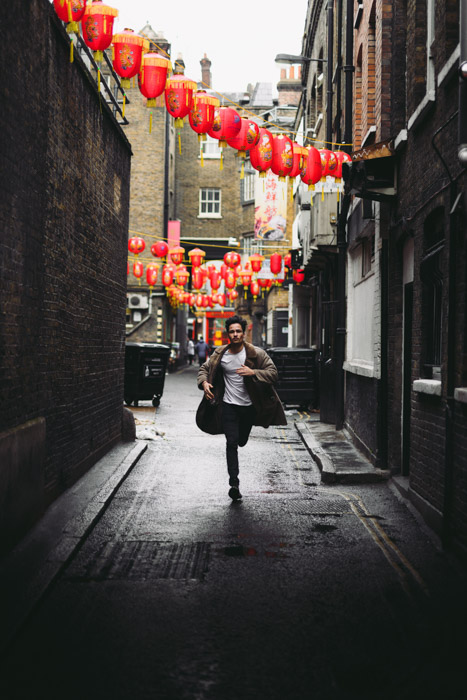 A man running down an alleyway towards the camera, a string of Chinese lanterns above him.