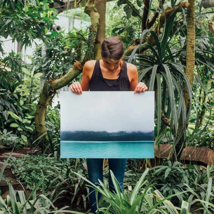 A man holding up a large printed photograph in an outdoor, forest setting - examining megapixels and how much do you need.
