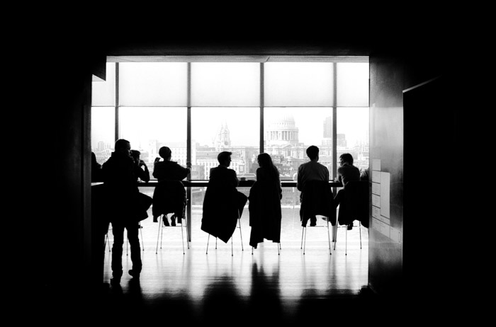 An atmospheric black and white photo looking into a a classroom or office full of people at desks. What Is a Megapixel and How Many Do You Really Need?