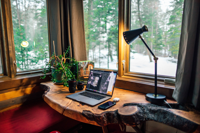 photo of a laptop on a wooden desk by the window